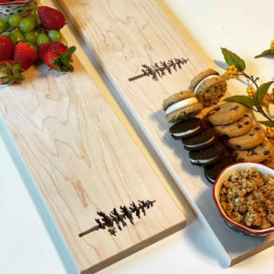 two maple rectangle grazing boards with spruce tree cutouts. One board with fruit, one with cookies